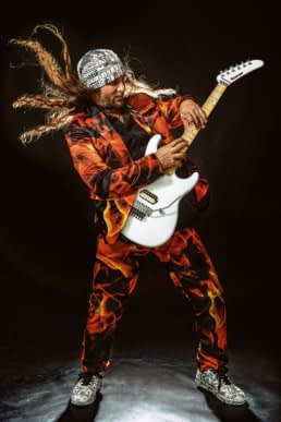 el amir en escena haciendo tapping en una guitarra kramer